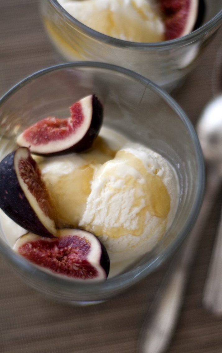 Two individual servings of homemade ice cream topped with sliced fresh figs and local honey