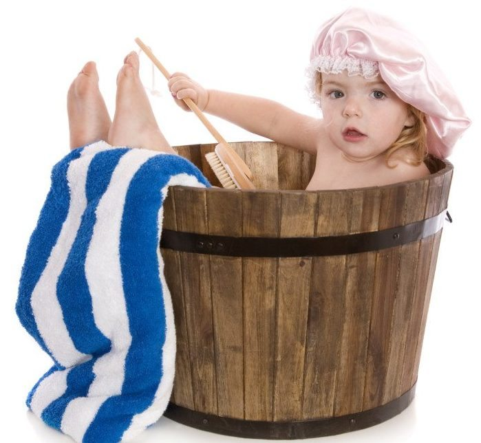 A cute two year old girl having a bath in a wooden barrel tub. Isolated on white.