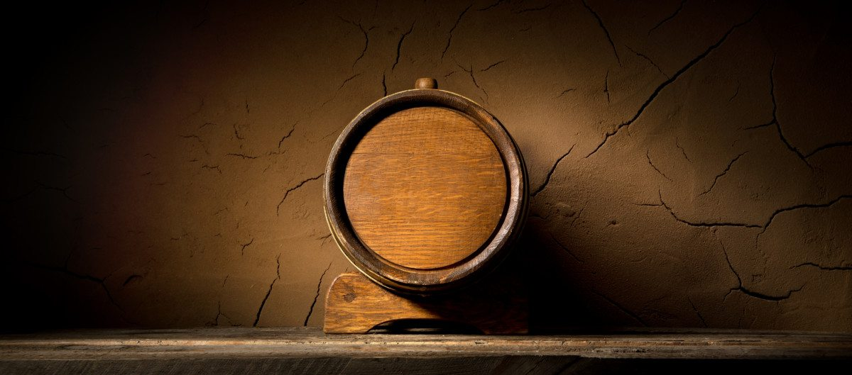 Wooden cask near clay wall in cellar